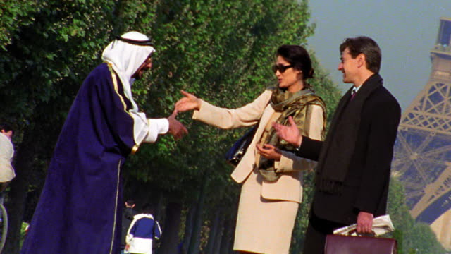 vídeos y material grabado en eventos de stock de canted zoom out arab man in robes + headdress shaking hands with businessman + woman by eiffel tower - mujer con grupo de hombres