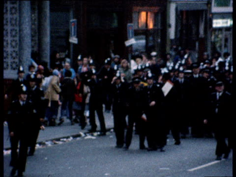 vídeos de stock e filmes b-roll de zoom out as lines of police officers carrying shields march through street then run as stones and objects rain down during disturbances at notting... - notting hill