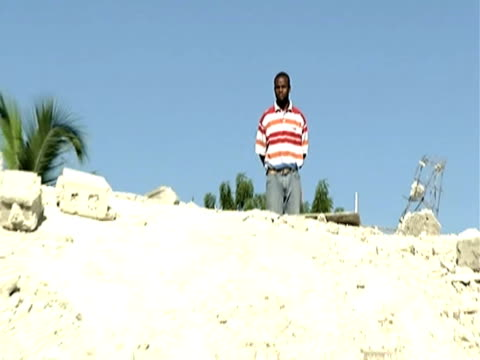 vídeos de stock e filmes b-roll de zoom out as man stands on top of large pile of rubble and examines destruction following devastating earthquake haiti 14 january 2010 - hispaniola