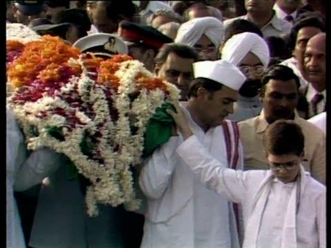 stockvideo's en b-roll-footage met zoom out as rajiv gandhi helps carry his mother indira gandhi's coffin through crowds of mourners delhi 1984 - assassinatie