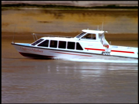 zoom out as small motor boat passes along river thames and under blackfriars railway bridge, london - motorboot stock-videos und b-roll-filmmaterial