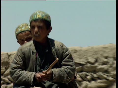 zoom out as two children ride horseback past stone walled afghan village afghanistan - pferdeartige stock-videos und b-roll-filmmaterial