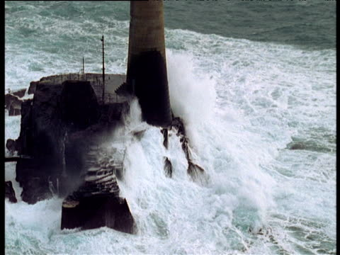 zoom out as waves crash at base of longships lighthouse, cornwall - lands end cornwall stock videos and b-roll footage