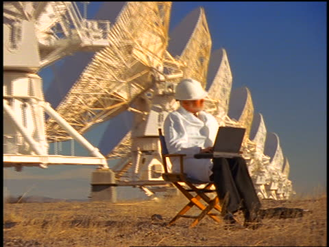vídeos de stock, filmes e b-roll de zoom out bearded scientist sitting with laptop computer in front of vla radio telescope dishes / new mexico - 1990 1999