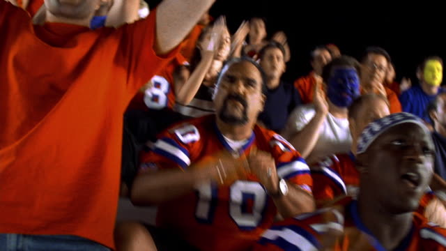 SHAKY MS zoom out Black man cheering with other football fans in bleachers during football game
