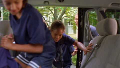 vidéos et rushes de ms zoom out black woman opening minivan door + four girls in soccer uniforms getting in - entrée