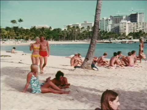 1969 zoom out blonde couple in swimsuits walking on beach with people sitting / hawaii / travelogue - bikini stock-videos und b-roll-filmmaterial