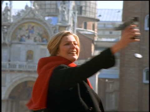 vidéos et rushes de zoom out blonde woman holding digital video camera spinning around in piazza san marco / venice, italy - 1990 1999
