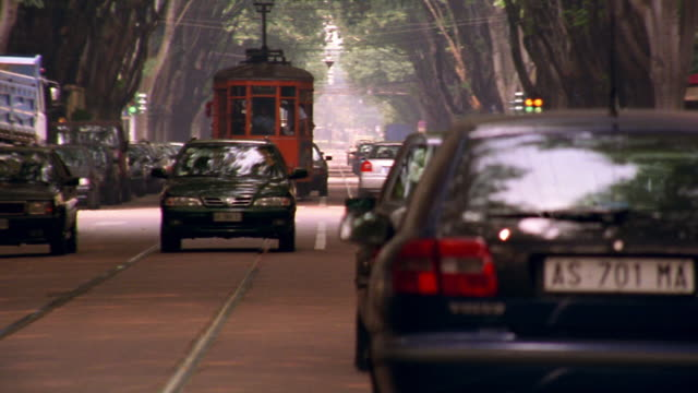 zoom out cars passing street trolley on tree covered street / Milan, Italy