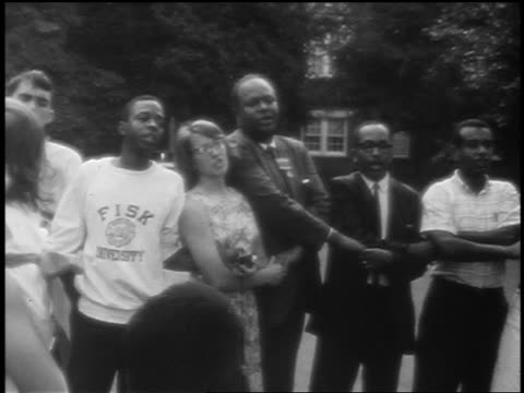 B/W 1965 zoom out circle of civil rights activists holding hands singing We Shall Overcome in street