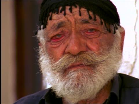vidéos et rushes de zoom out close up portrait senior man with black cap + red eyes looking at camera / crete, greece - moustache