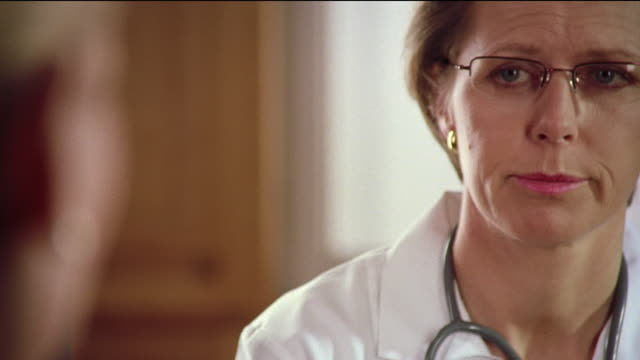 Zoom out close up rack focus from face of female doctor talking to mature female patient looking upset