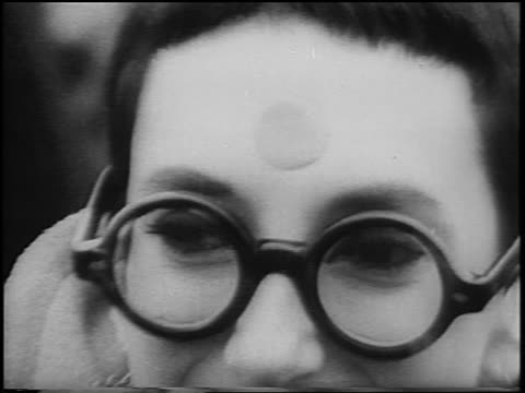 B/W 1967 zoom out close up woman with thick eyeglasses dot on forehead at antiwar rally in Central Park / NYC