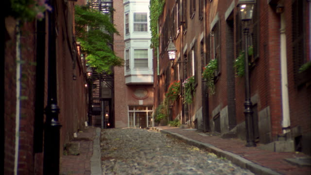 Zoom out cobblestone alley w/brownstone buildings in Boston / MA