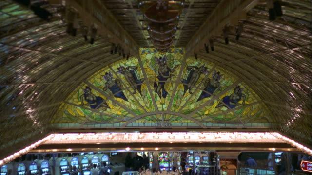 zoom out colored glass on ceiling to high angle people gambling in casino / las vegas - casino interior stock videos & royalty-free footage