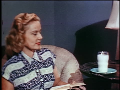 1948 zoom out pan couple takes glasses of milk from table, toast each other + drink in living room / ind. - milk stock-videos und b-roll-filmmaterial