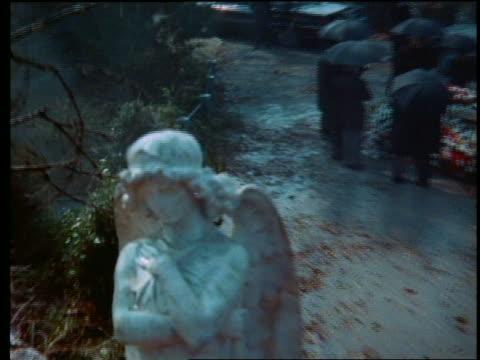 zoom out crane shot from close up of marble angel to small funeral in rainy cemetery / zoom in - ängel bildbanksvideor och videomaterial från bakom kulisserna