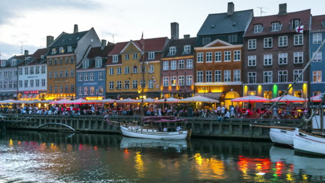vídeos de stock e filmes b-roll de zoom out day to night tl: crowds enjoying restaurants bars at dusk among colorful traditional houses in copenhagen nyhavn city, denmark - região de oresund