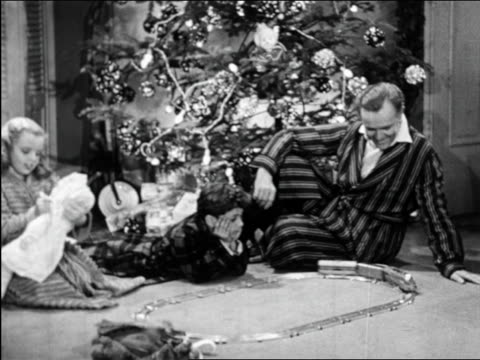 b/w 1950 zoom out family playing with train set on xmas morning / educational - christmas morning stock videos & royalty-free footage