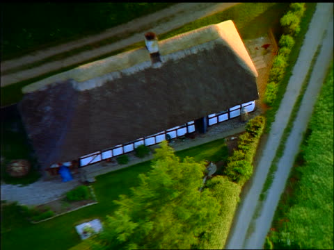 aerial zoom out farmhouse with thatched roof + green field / faborg, fyn, denmark - thatched roof stock videos & royalty-free footage