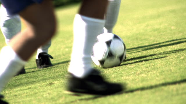 ms zoom out feet of soccer player dribbling ball away from opposing players in game - studded stock videos and b-roll footage