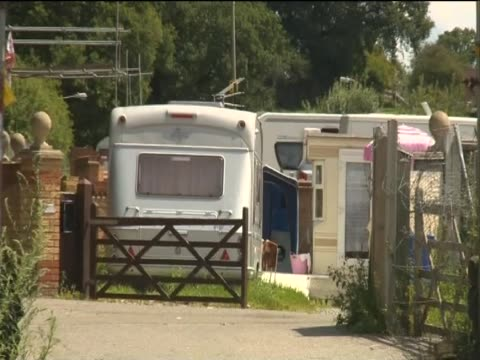 zoom out from a caravan in the entrance of dale farm essex uk - デールファーム点の映像素材/bロール