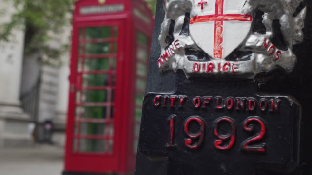 Zoom out from a decorative coat of arms on the base of a lamppost on the City of London.