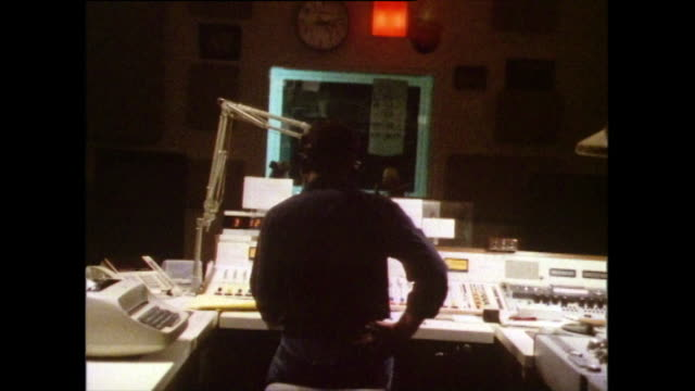 zoom out from a dj sitting at a radio mixing desk; 1985 - ラジオ放送点の映像素材/bロール