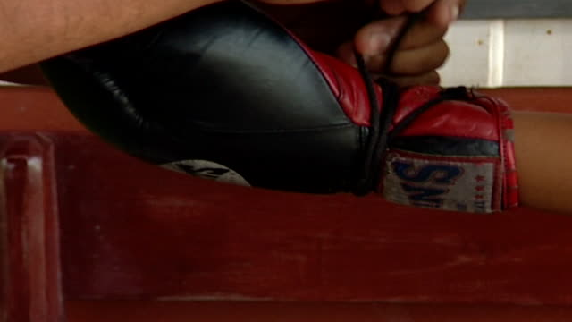 zoom out from a man lacing up a muay thai female boxer's red and black boxing glove. muay thai, known as the art of eight limbs, is a national sport... - human leg stock videos & royalty-free footage