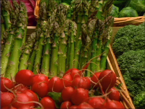 zoom out from asparagus to water being sprayed on vegetables