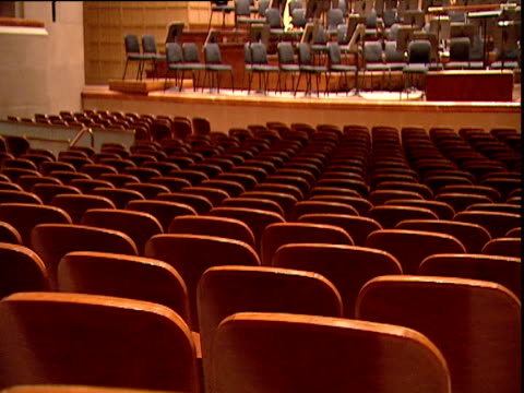 Zoom out from backs of red seats to interior of symphony hall including stage and organ pipes