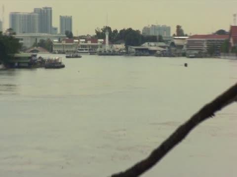 zoom out from bangkok's chao phraya swollen river and submerged surroundings - チャオプラヤ川点の映像素材/bロール