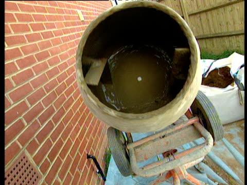 vídeos y material grabado en eventos de stock de zoom out from barrel of revolving cement mixer builder lays slabs for garden patio shovel full of cement england - cement mixer