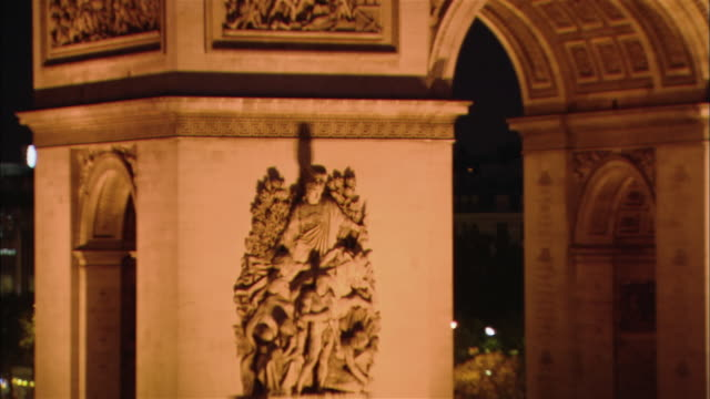 zoom out from bas-relief on arc de triomphe to view of arch illuminated on place de l'etoile at night / paris, france - bas relief stock videos & royalty-free footage