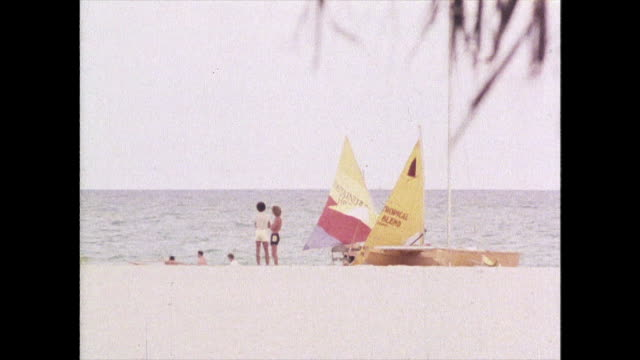 zoom out from beach in miami to sunbathing tourists; 1980 - miami stock videos & royalty-free footage