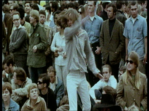 vídeos de stock e filmes b-roll de zoom out from bearded hippy surrounded by crowd of people as he dances wildly at love in 1967 - hippie