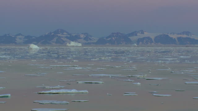 Zoom out from beautiful midnight sun landscape Greenland