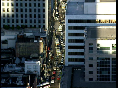 Zoom out from busy city traffic including buses to skyscrapers of business district San Francisco