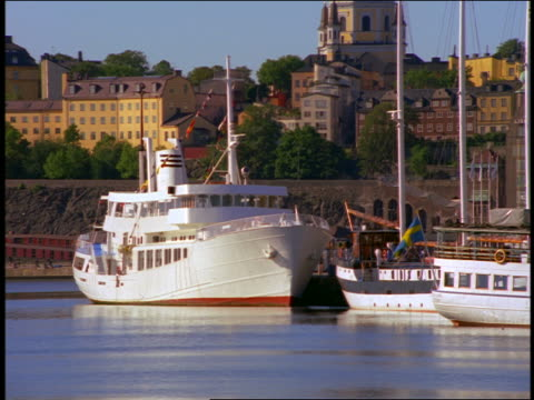 zoom out from cabin cruisers + ferries docked with city buildings in background / gamle stan / stockholm, sweden - stockholm stock videos & royalty-free footage