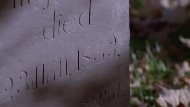 Zoom out from carved inscription to gravestones surrounded by fallen leaves, Granville, New York Available in HD.