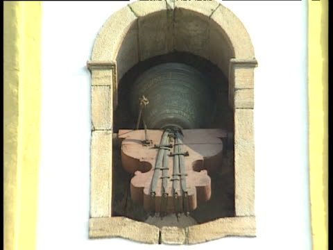zoom out from church bell ringing to line of worshippers in street below ouro preto brazil - 宗教上のシンボル点の映像素材/bロール