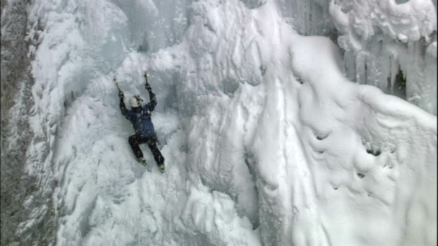 zoom out from climber ascending craggy ice wall, johnston canyon, canadian rocky mountains park, canada - 崖点の映像素材/bロール