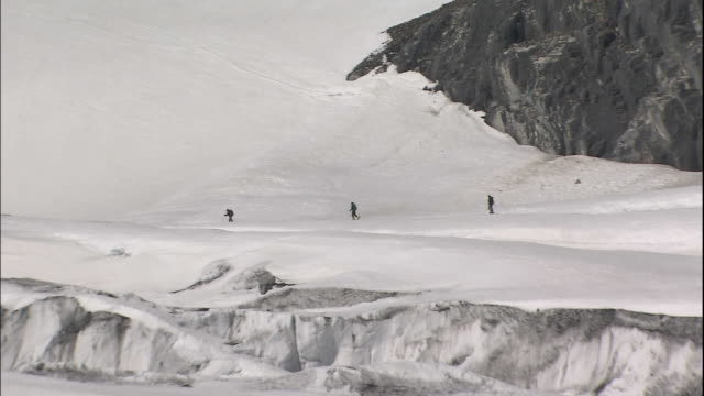 zoom out from climbers crossing ice field to expanse of athabasca glacier, canadian rocky mountains park, canada - felswand stock-videos und b-roll-filmmaterial