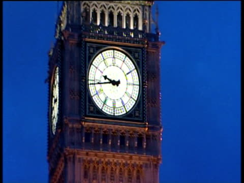 Zoom out from clock face of Big Ben against clear night time sky to lit up Houses of Parliament