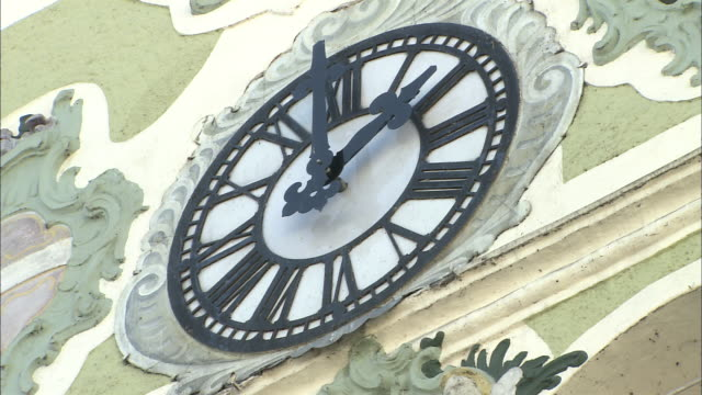 Zoom out from clock on tower of town hall with chiming carillon