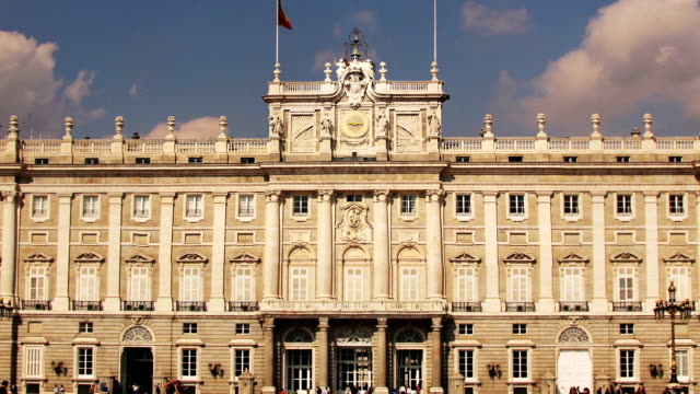 zoom out from clock over entrance to palacio real at 9:15 a.m. to view of pedestrians passing facade on plaza de la armeria in fast motion / madrid, spain - palace stock videos & royalty-free footage