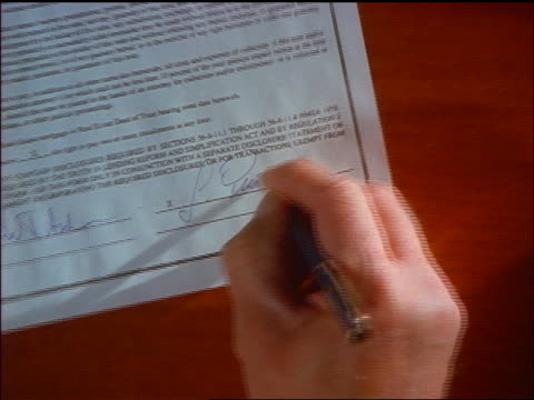 OVERHEAD zoom out from close up businessman signing contract + shaking hands with other man