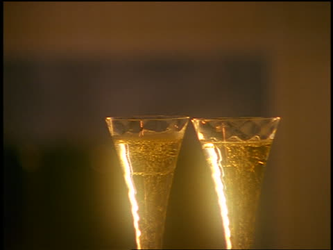 vidéos et rushes de zoom out from close up champagne being poured into two glasses on table with candles + mask / fireplace in background - 1990 1999