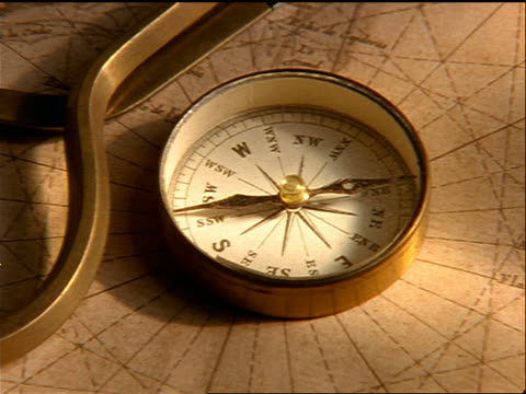 zoom out from close up of directional compass + distance compass on top of old nautical map of new world - inquadratura dall'alto di un tavolo video stock e b–roll