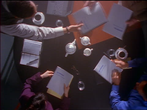 overhead zoom out from close up of man pouring coffee to businesspeople working at conference table with booklets - fare una pausa video stock e b–roll